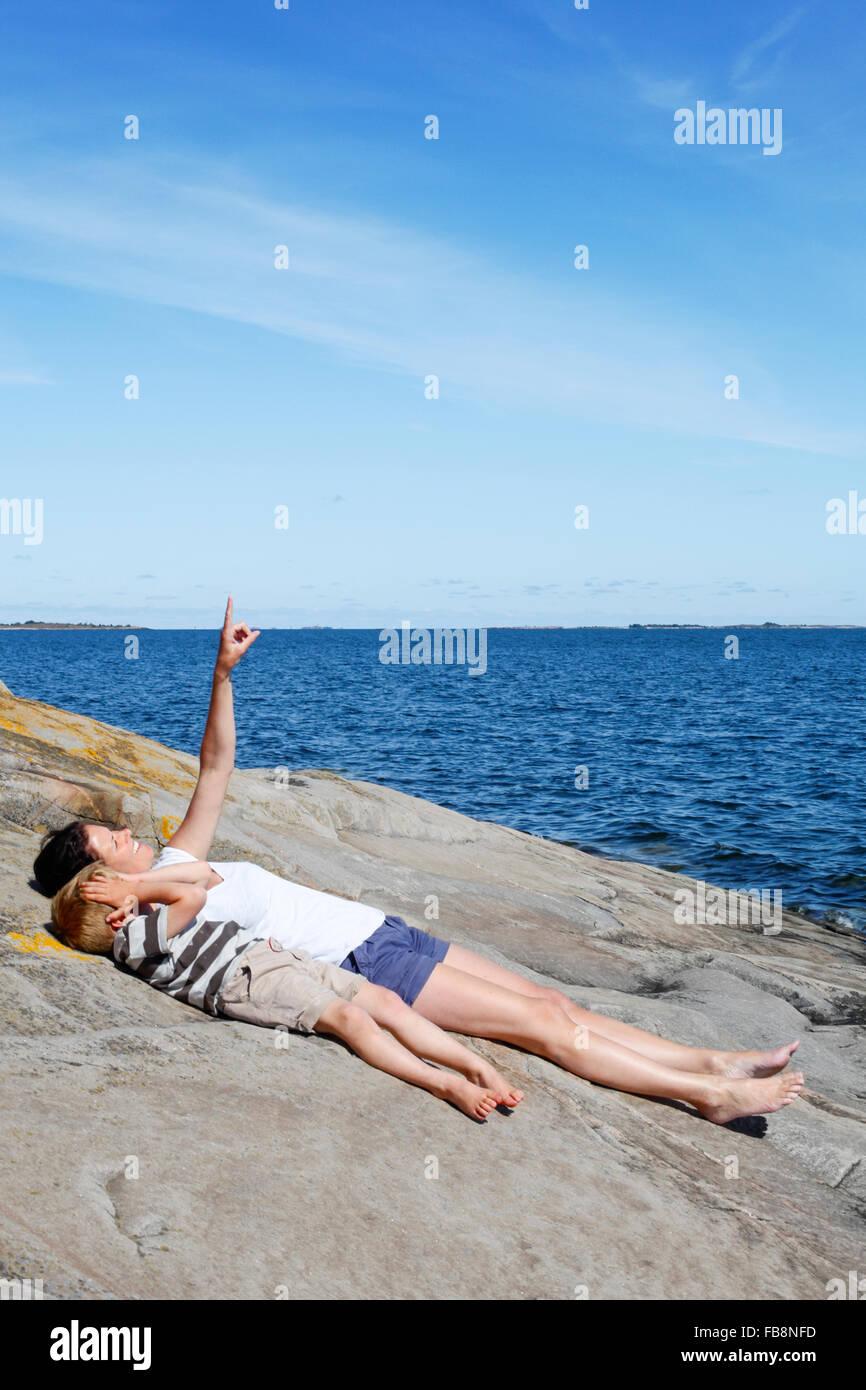 Sweden, Uppland, Runmaro, Barrskar, Mother with son (4-5) lying down on seaside - Stock Image