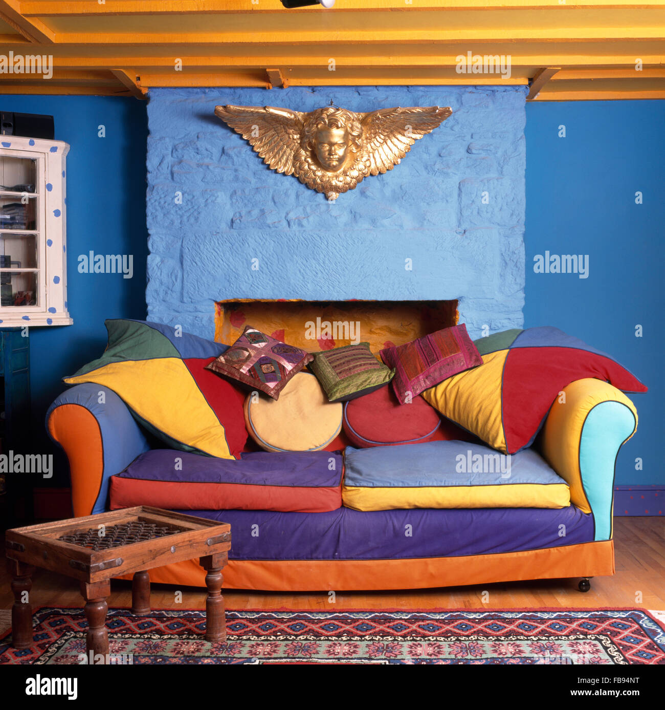Gold Cherub Above A Vibrant, Multi Colored Sofa In A Bright Blue Nineties  Cottage Living Room