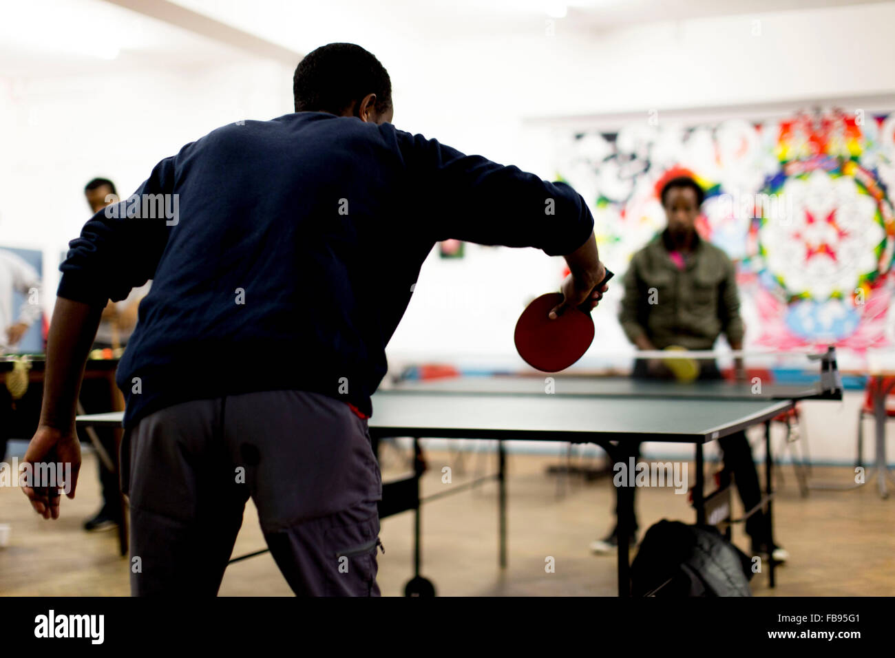 unidentifiable young men play table tennis  at a UK community centre - Stock Image