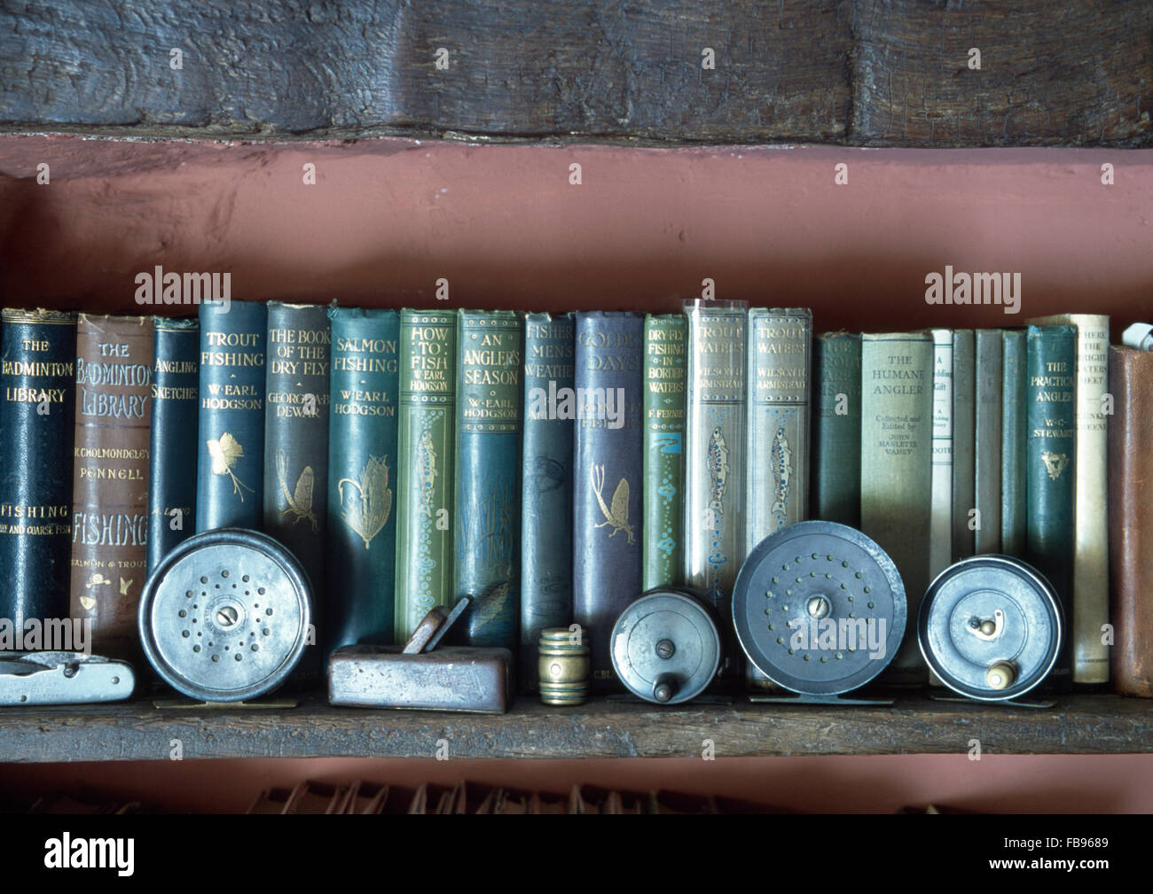 Collection of hardback vintage books on angling on shelf with antique angling equipment - Stock Image