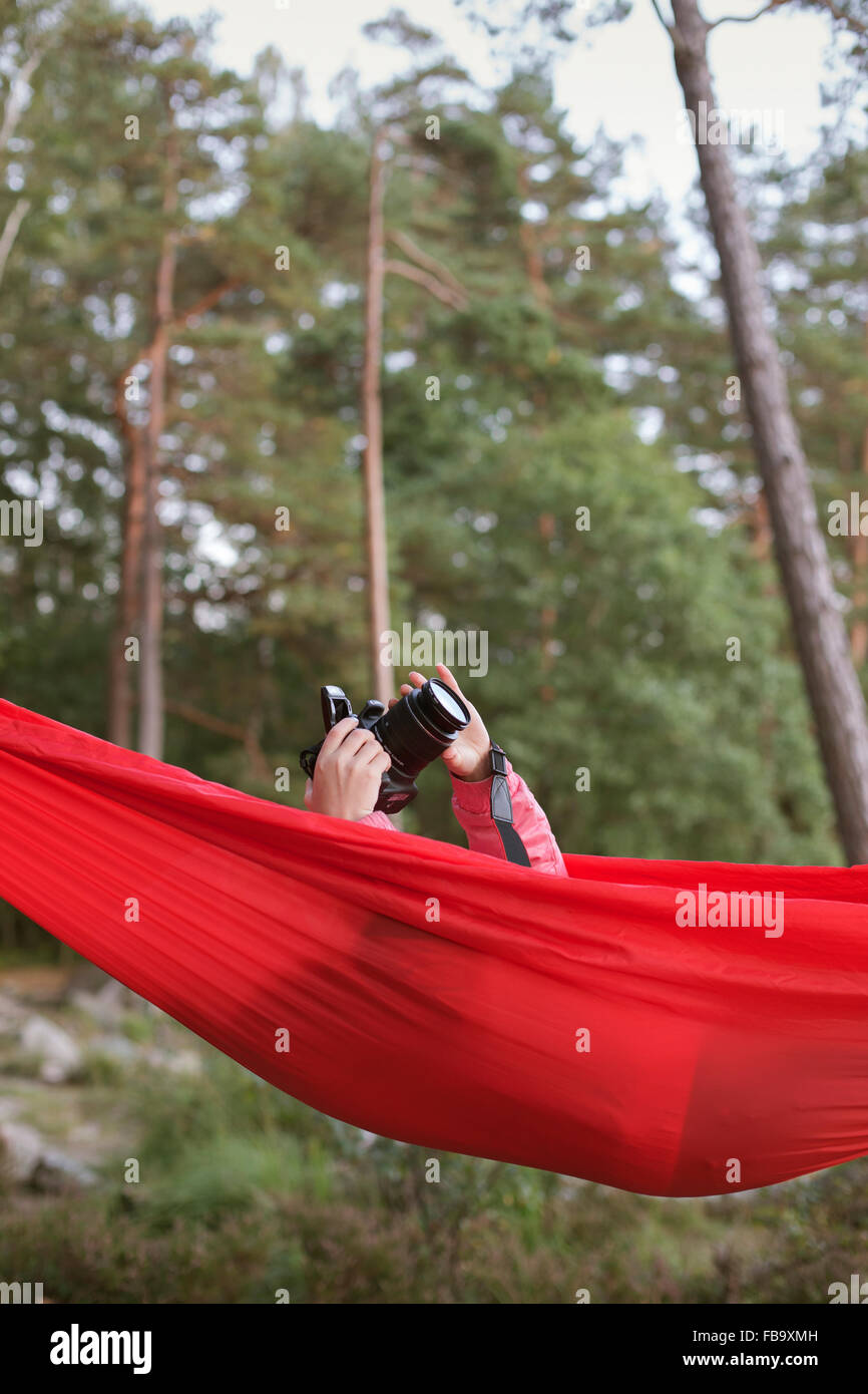 Sweden, Vastergotland, Lerum, Girl (10-11) lying in hammock and taking pictures with camera - Stock Image