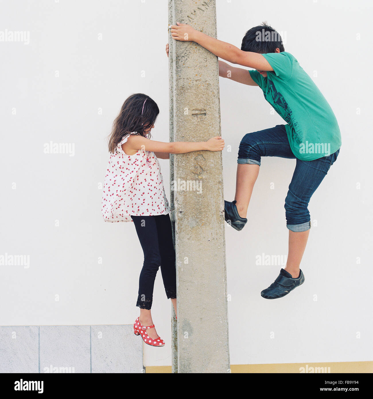 Portugal, Boy (10-11) and girl (6-7) climbing post - Stock Image
