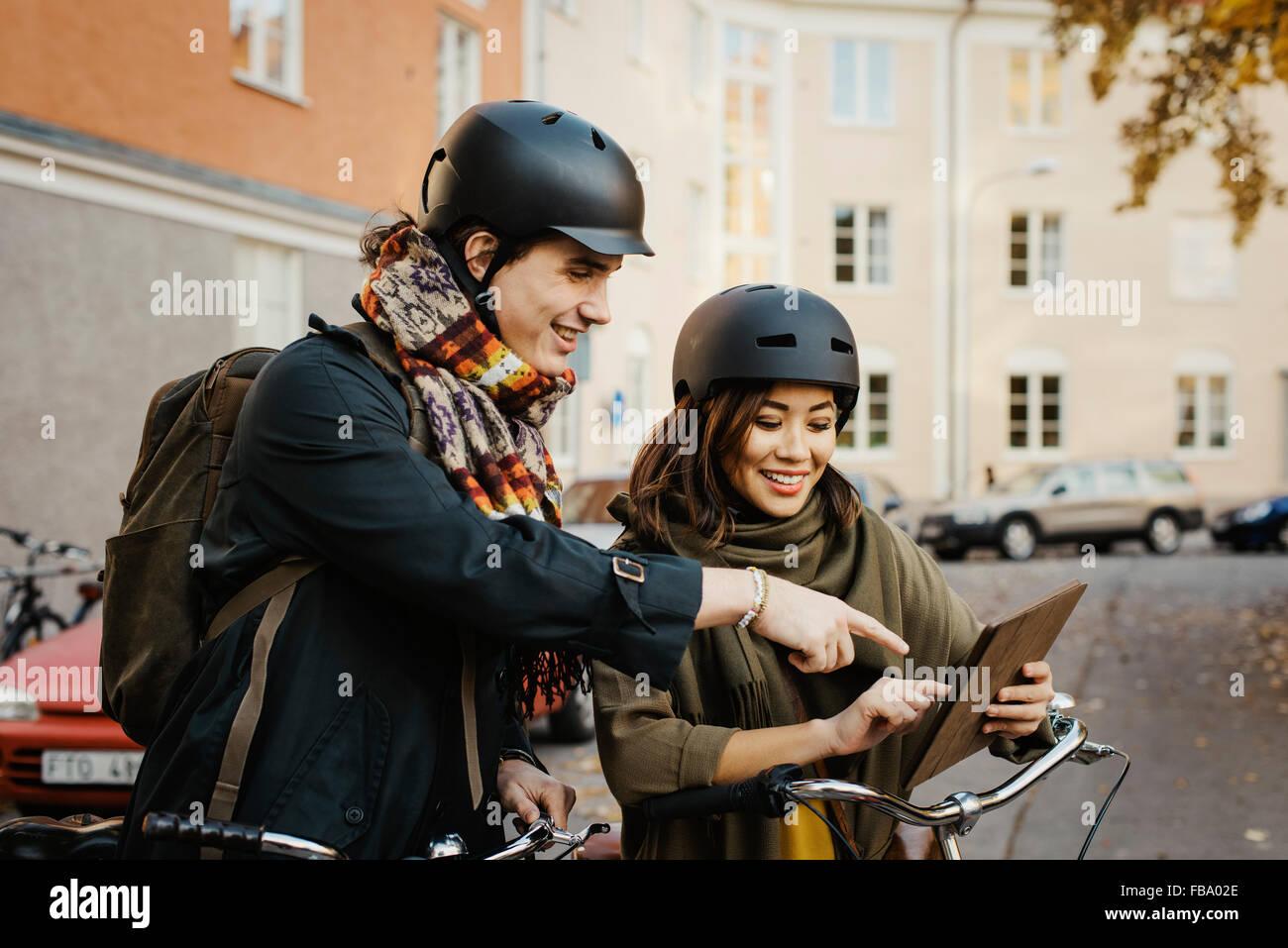 Sweden, Uppland, Stockholm, Vasastan, Rodabergsbrinken, Two young people looking at digital tablet smiling - Stock Image