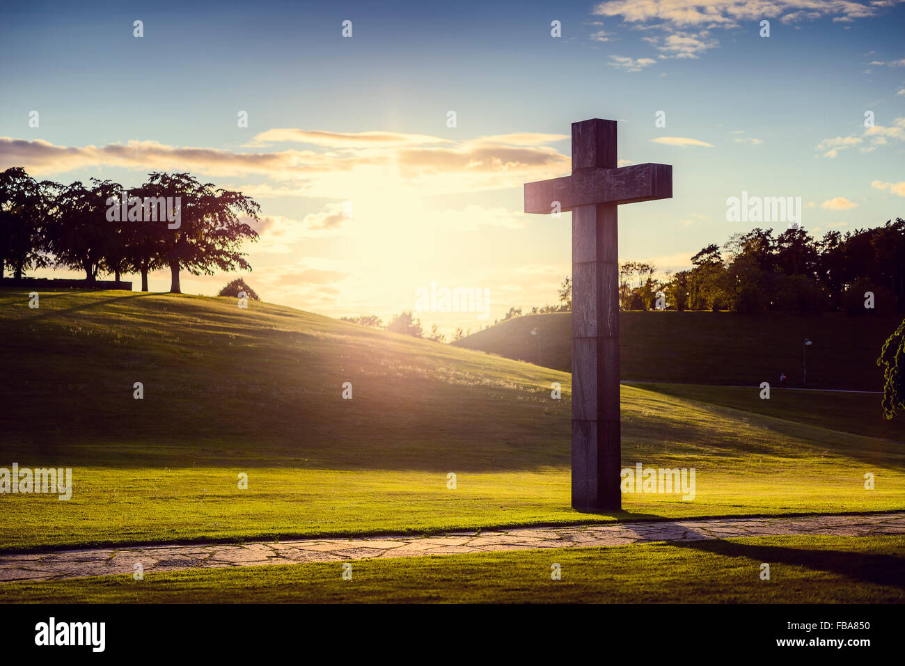 Sweden, Sodermanland, Stockholm, Gamla Enskede, Skogskyrkogarden, Cross in green valley at sunset - Stock Image