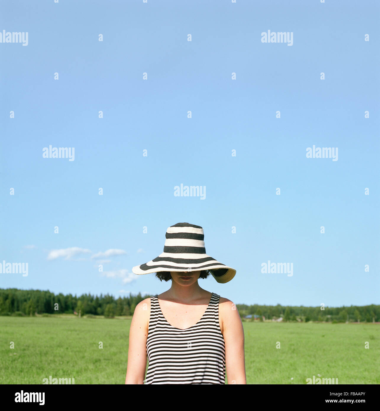 Finland, Uusimaa, Lapinjarvi, Woman wearing hat covering her face - Stock Image