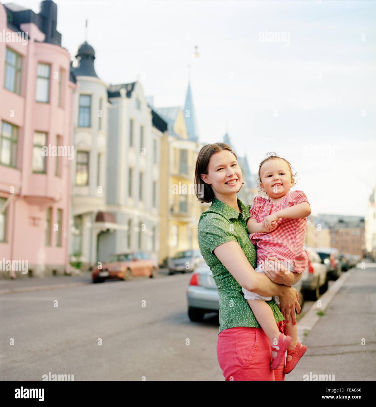 Finland, Uusimaa, Helsinki, Portrait of mother holding daughter (2-3) on street - Stock Image