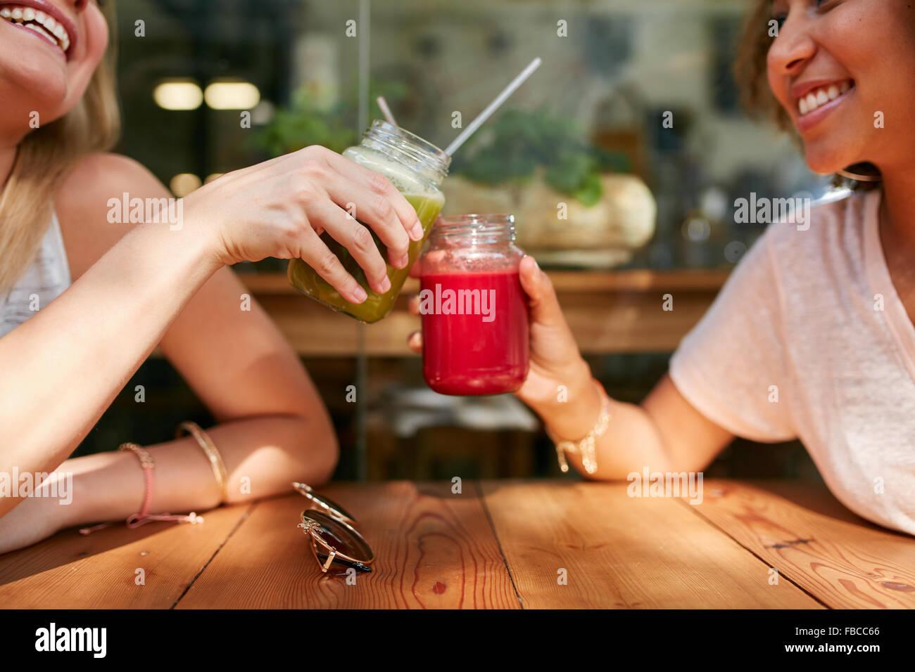 Close up shot of female friends toasting juice glasses at sidewalk cafe. Two happy women enjoying fresh drinks at - Stock Image