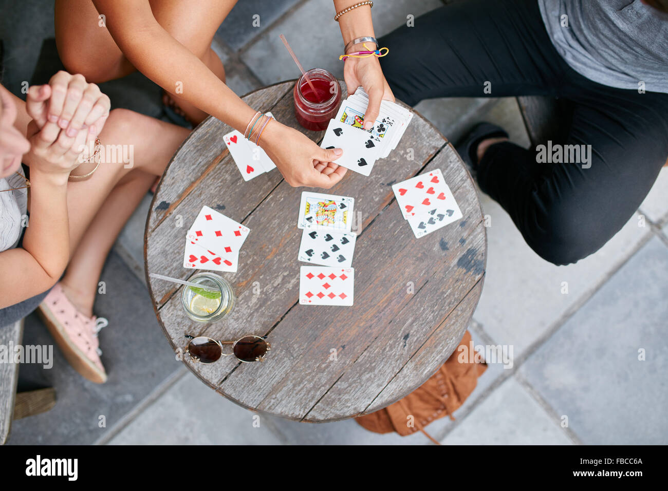 Top view of three young friends playing cards at cafe. Young people playing card game at coffee shop. - Stock Image