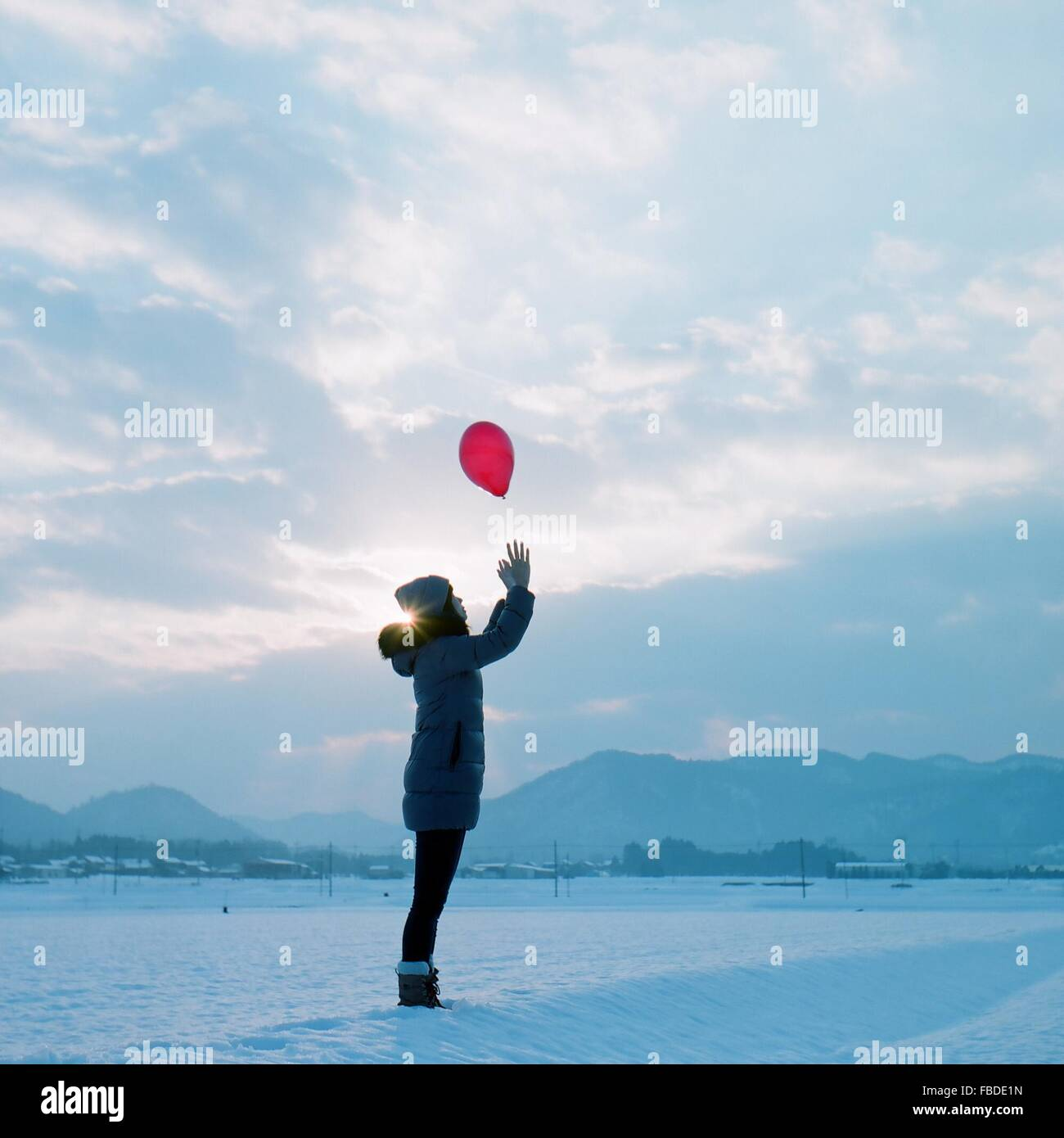Side View Of Girl In Warm Clothing Catching Red Balloon While Standing On Snowy Field - Stock Image
