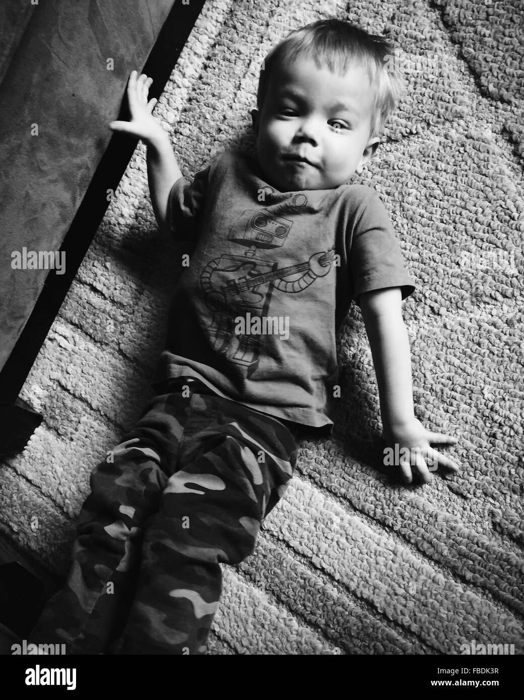 Boy Lying On Carpet - Stock Image