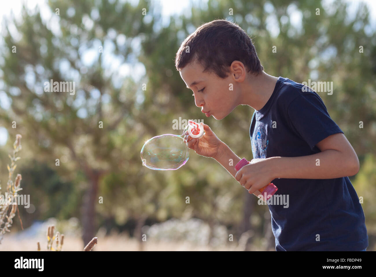 Boy Blowing Bubbles On Plants - Stock Image
