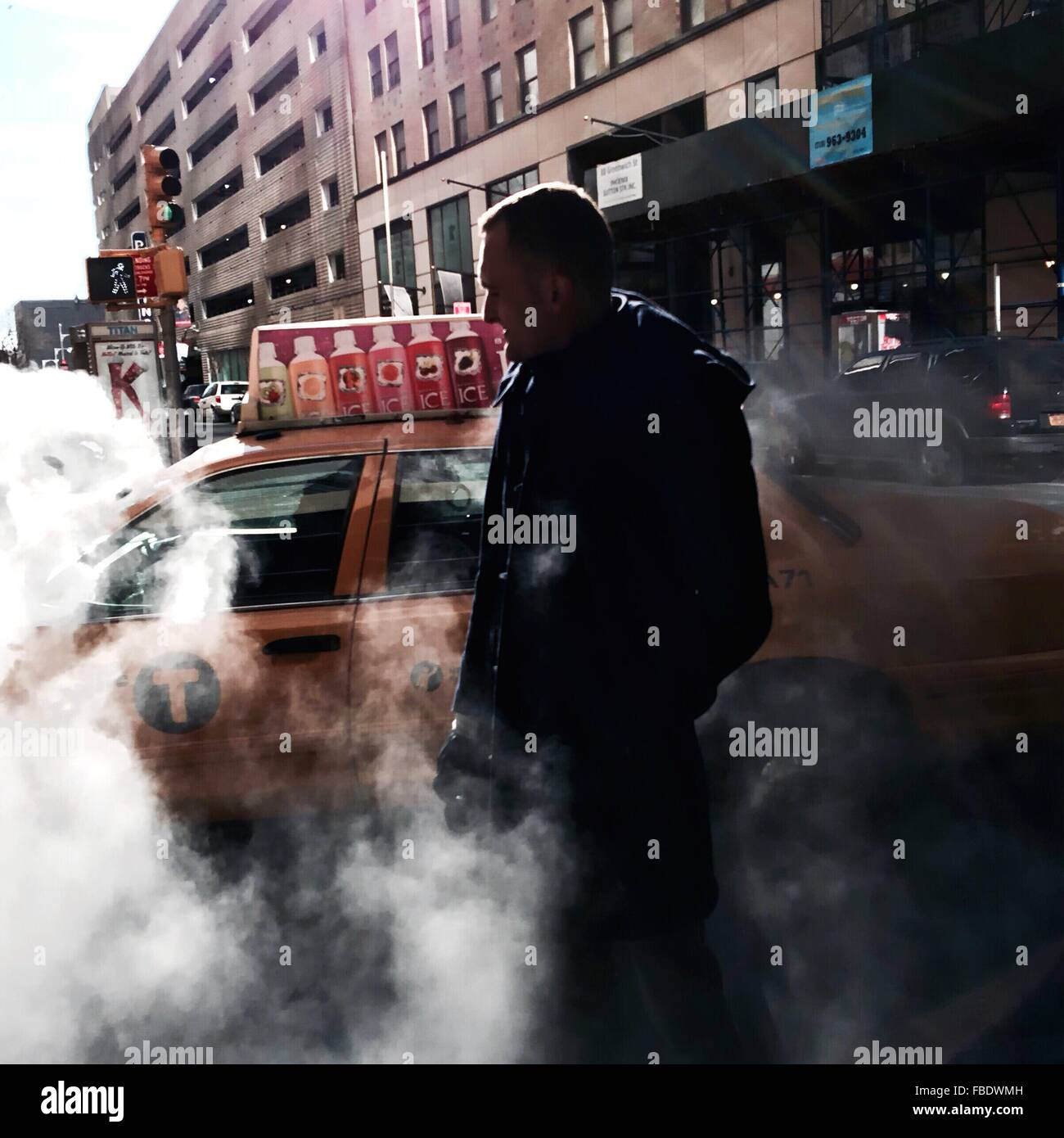 Mid Adult Man Surrounded By Smoke While Standing Against Car On Street - Stock Image