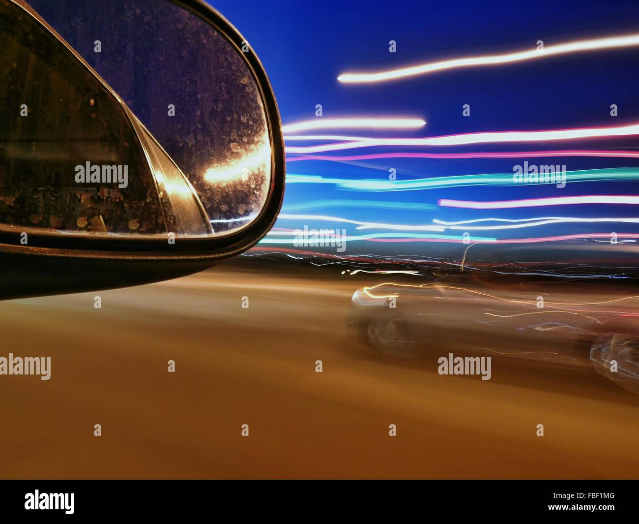 Side-View Mirror And Light Trails On Street At Night - Stock Image