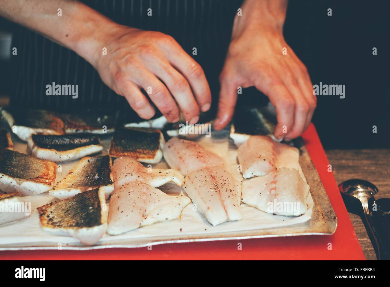 Cropped Hands Of Chef With Fish Meat At Commercial Kitchen - Stock Image