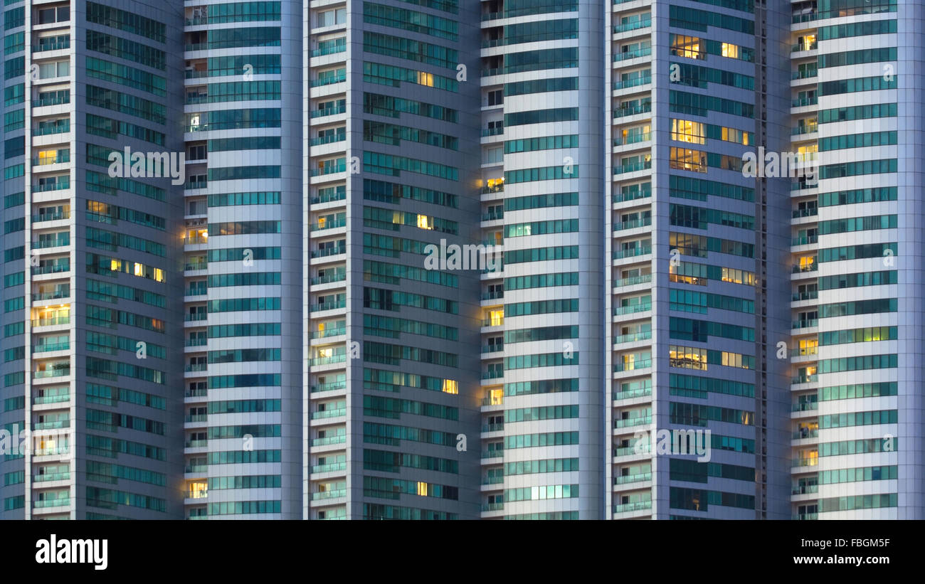 illuminated windows in a tall building at night - Stock Image