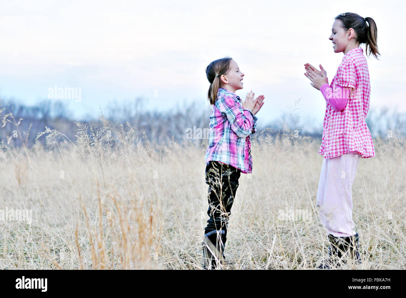 girls playing clapping hand games in field - Stock Image