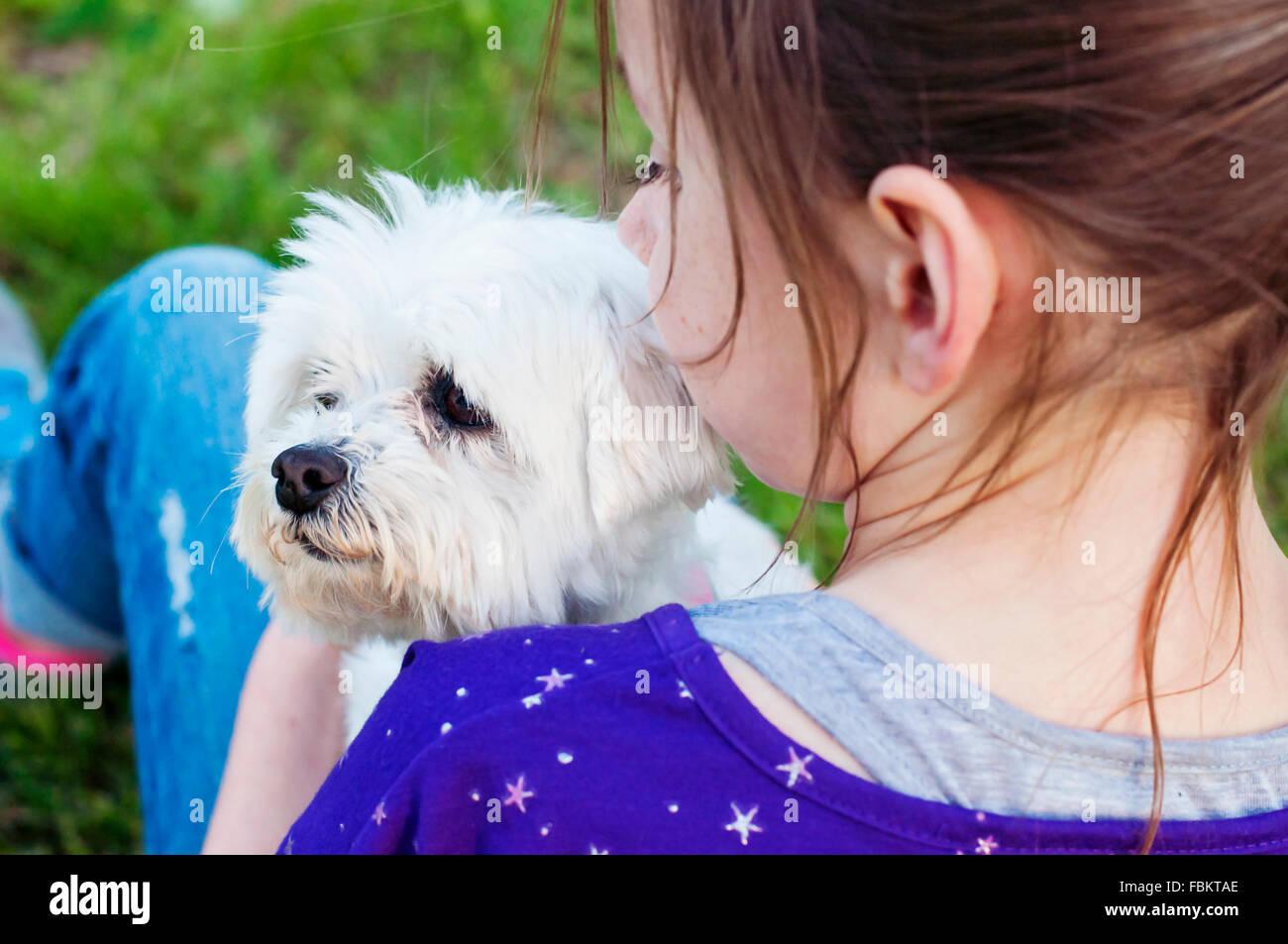 Girl holding dog - Stock Image