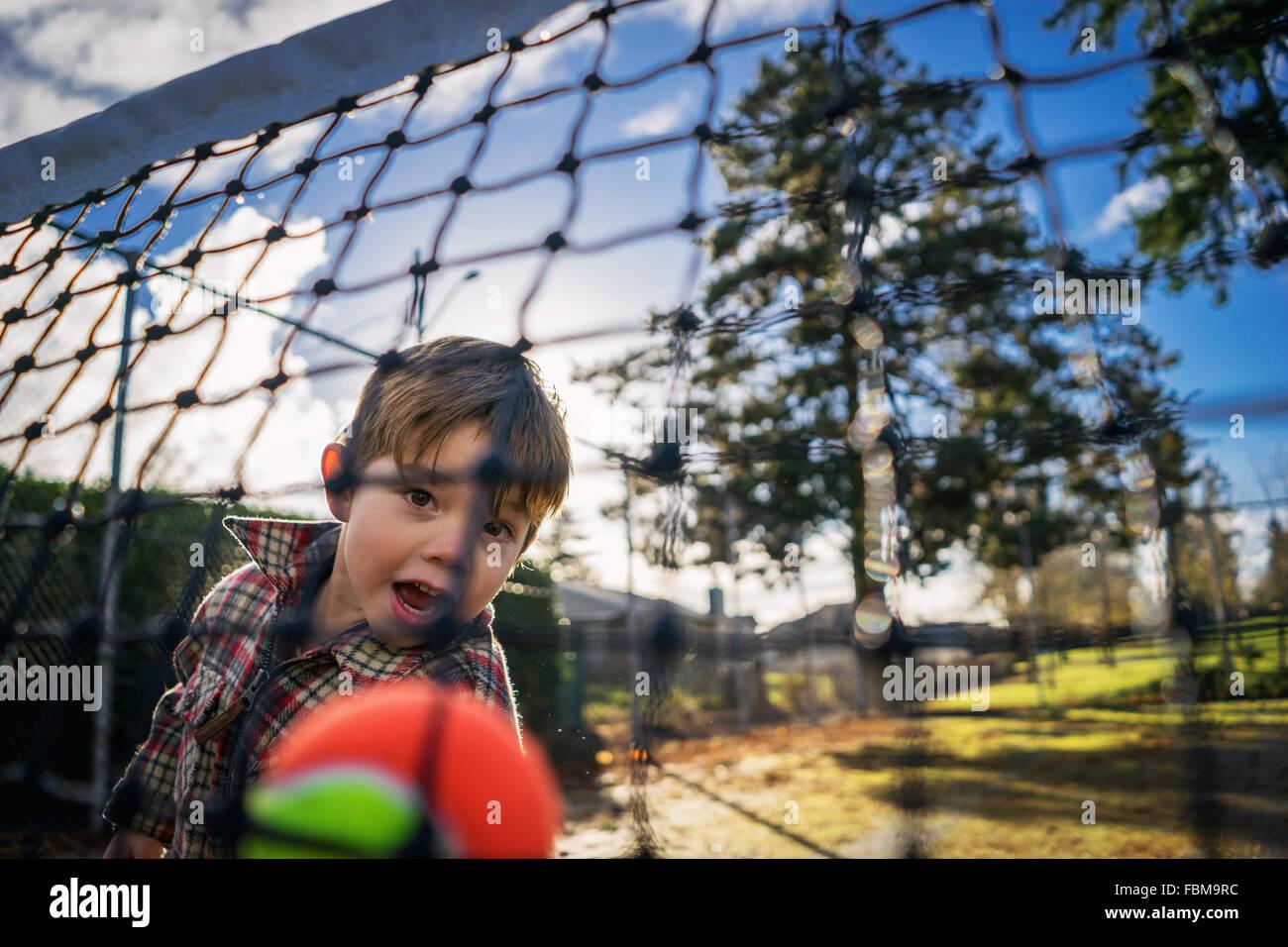 View through a net of a boy throwing tennis ball - Stock Image