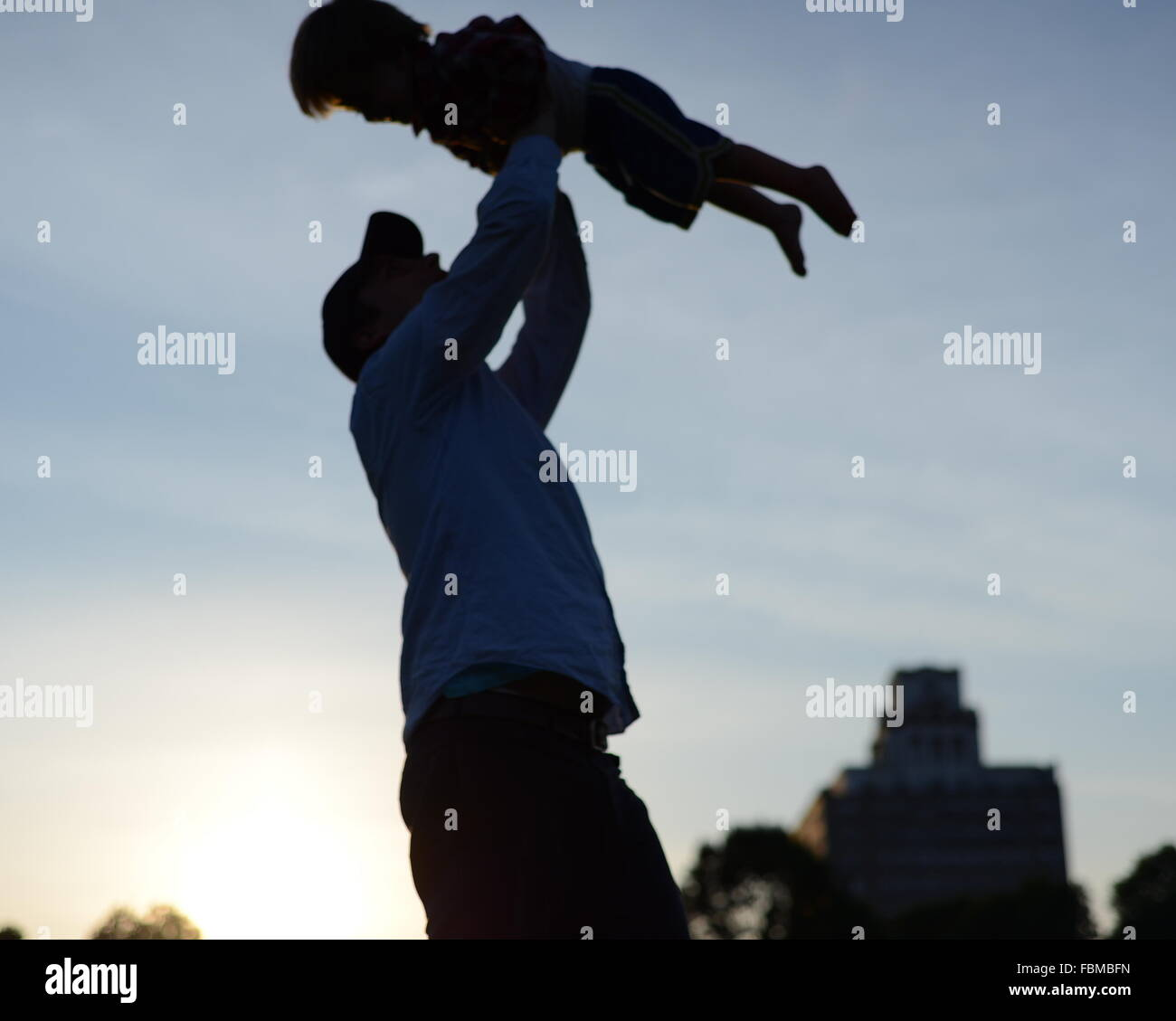 Low Angle View Of Man Carrying Baby Against The Sky - Stock Image