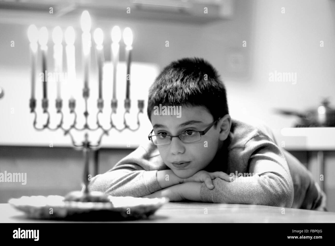 Cute Boy Looking At Lit Candles While Sitting On Table At Home - Stock Image
