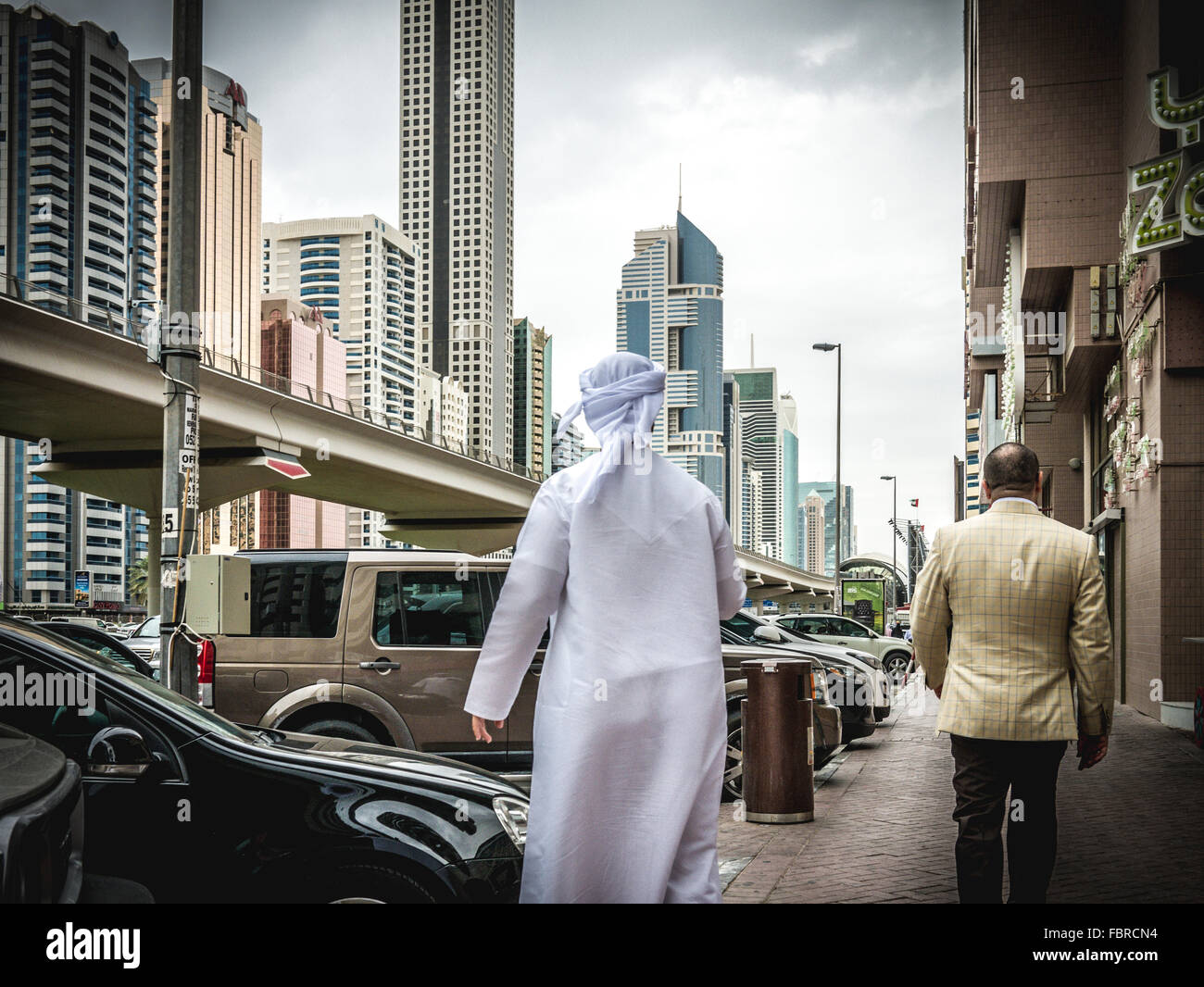 Arab man walking along busy Sheik Zayed Road - Stock Image
