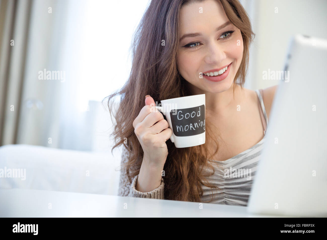 Smiling charming young woman using tablet and drinking coffee from white mug with black area for writing - Stock Image