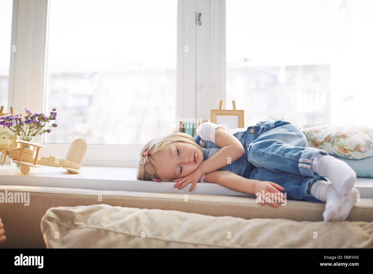 Sad little girl in denim overall lying on windowsill - Stock Image