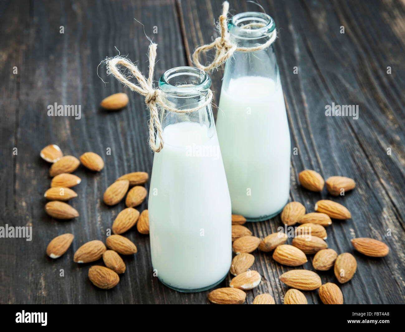 Almond milk in bottles with almond nuts on wooden background - Stock Image