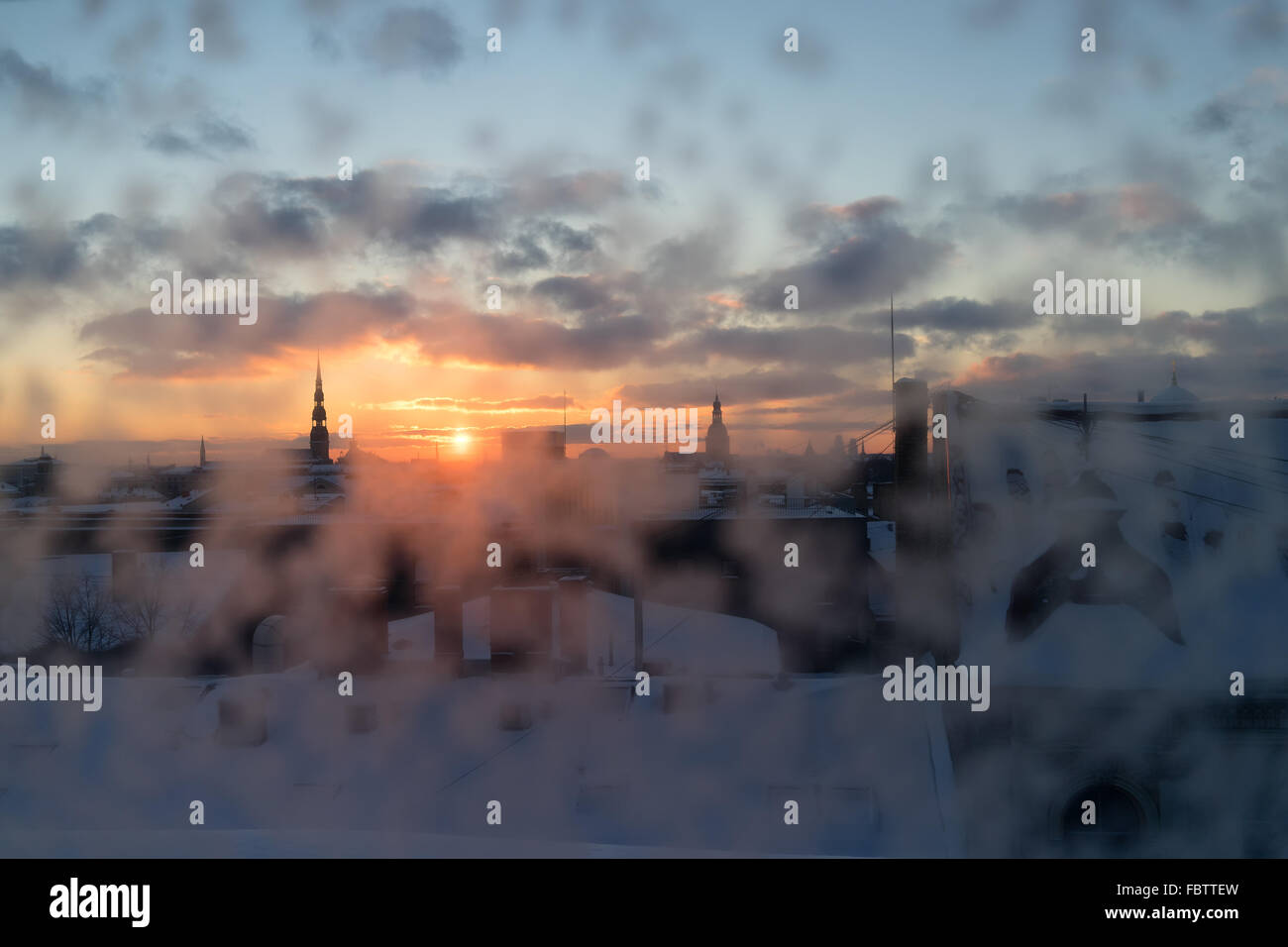 Roofs and churches of Riga in the winter through the snow-covered window at sunset. Latvia - Stock Image
