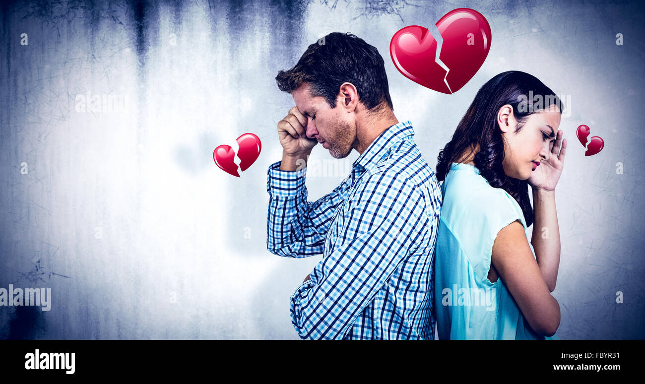 Composite image of depressed couple standing back to back - Stock Image
