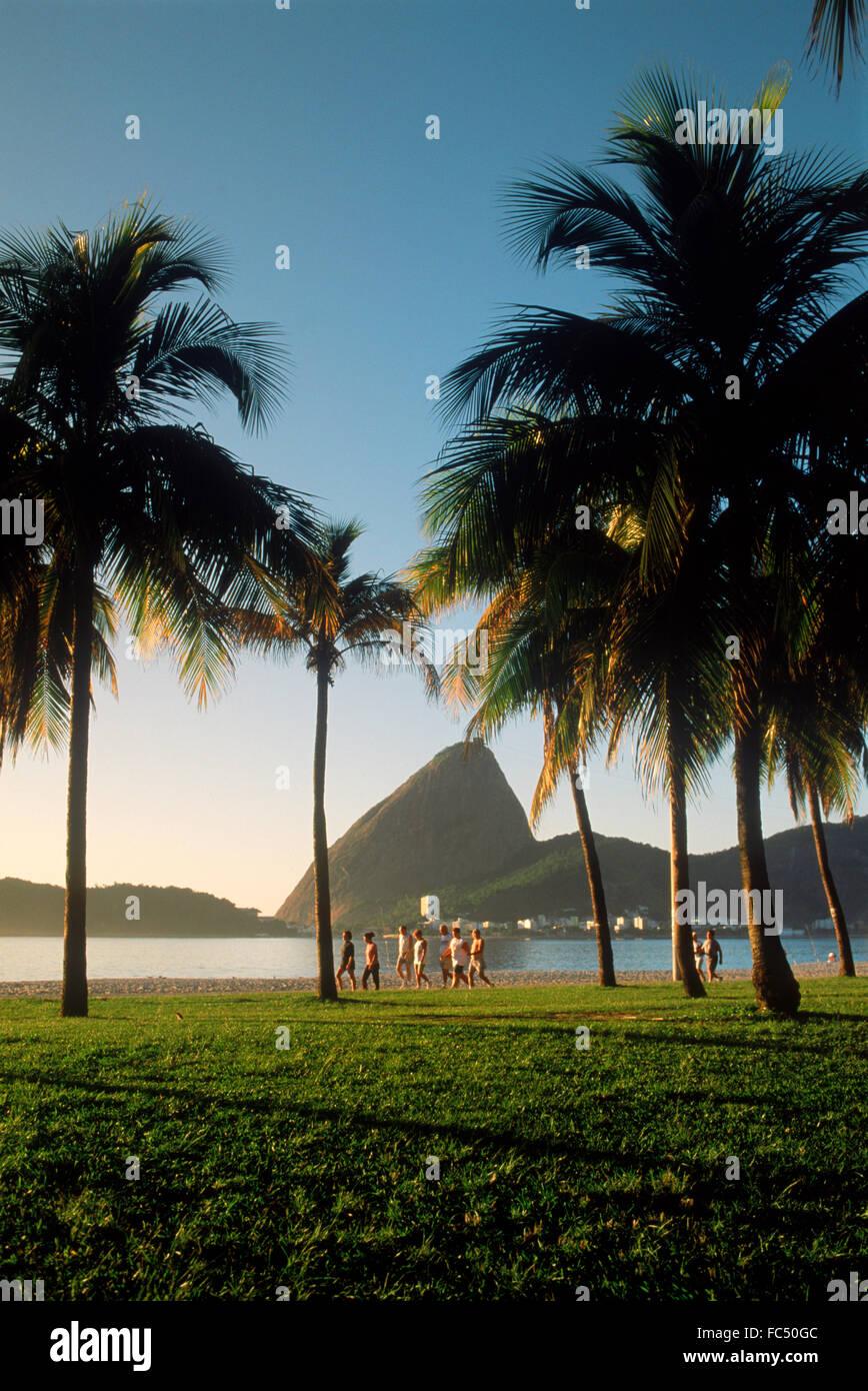 People taking morning jog and walk along Flamengo Beach near Sugar Loaf at sunrise in Rio de Janeiro Brazil - Stock Image