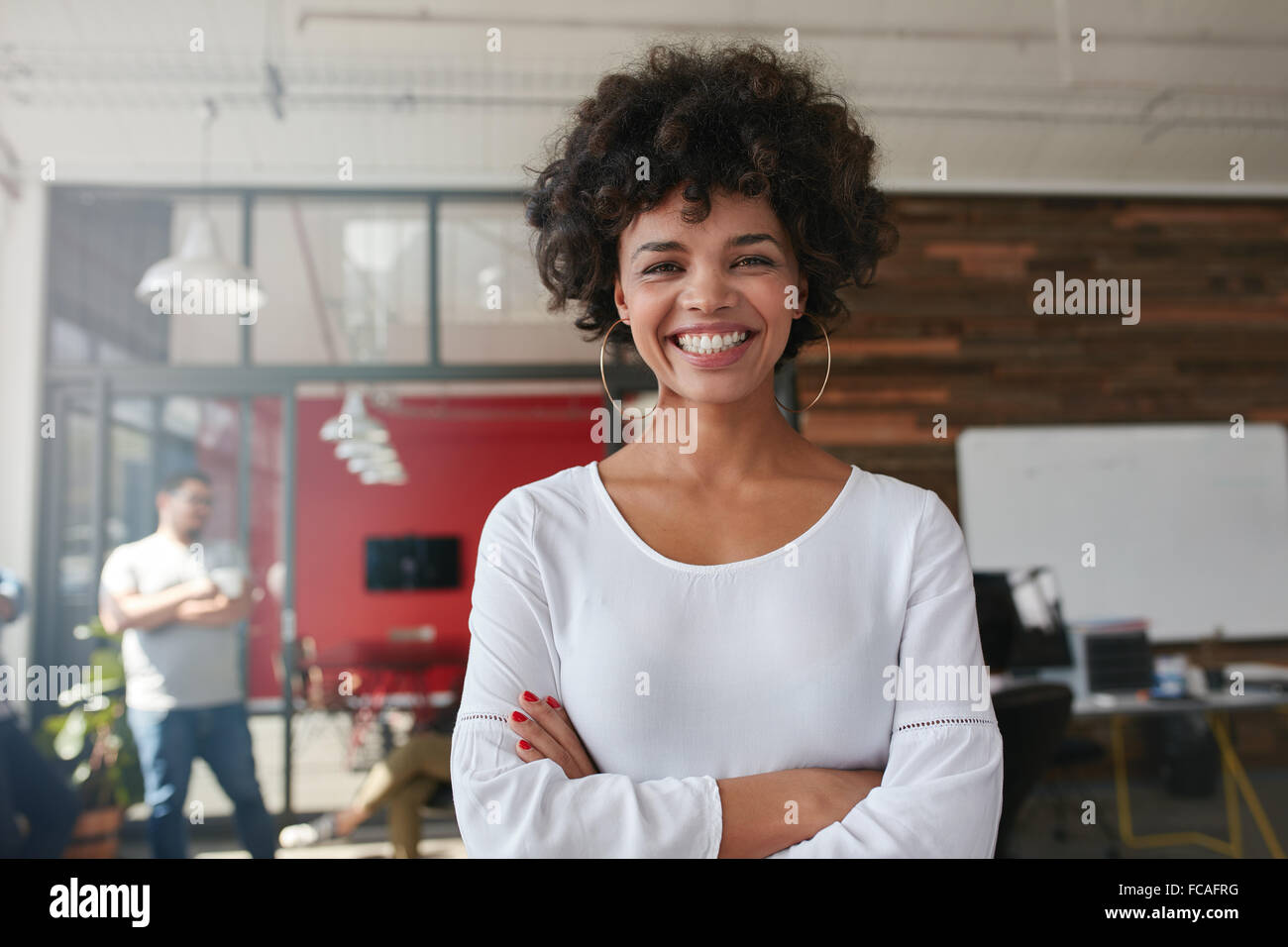 Smiling young woman standing with her arms crossed and looking at camera. She is standing in a modern office with - Stock Image