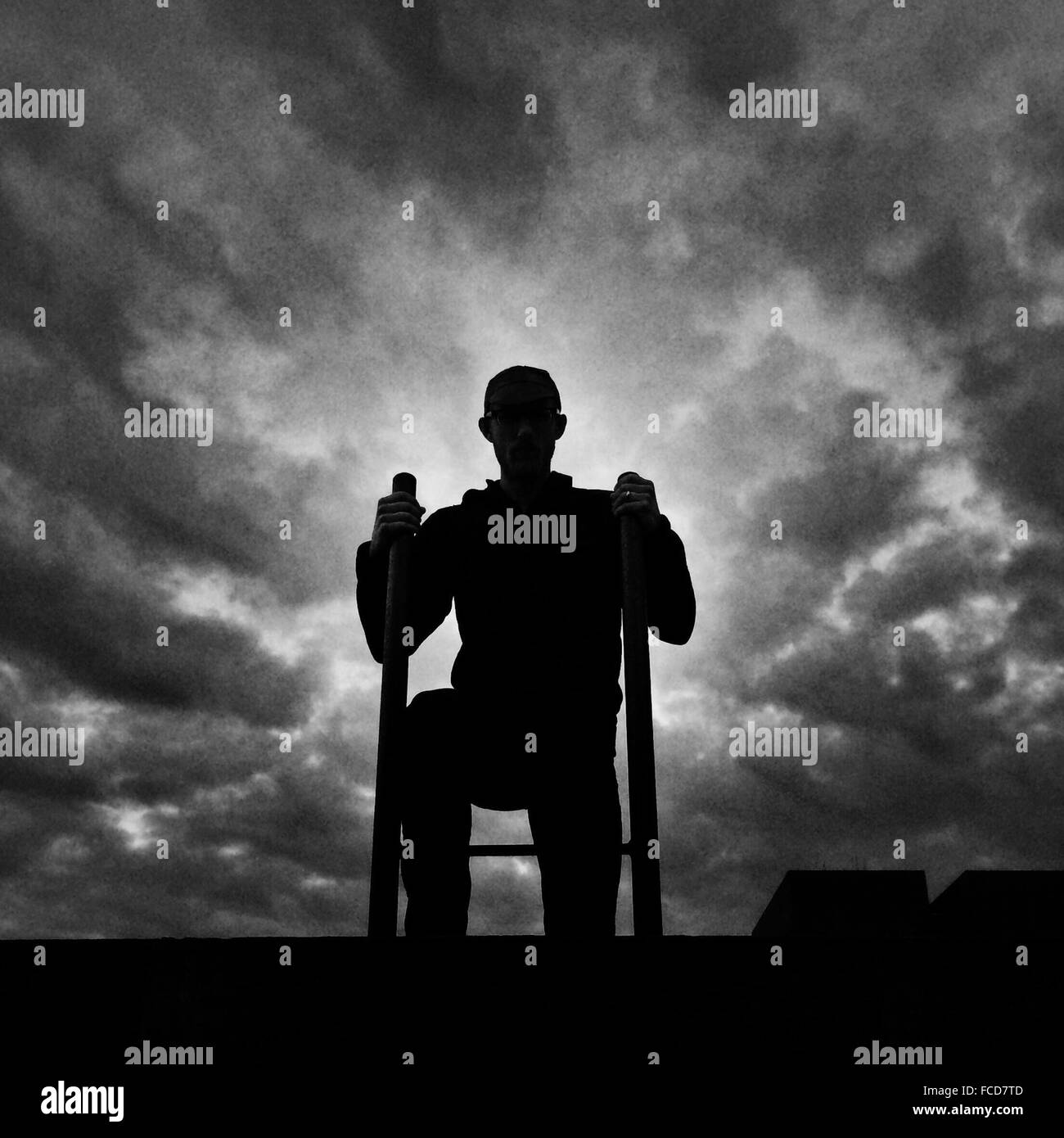 Man On The Roof Of A Building - Stock Image