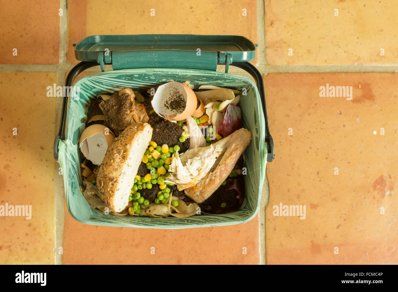 food waste - Indoor food recycling caddy full of kitchen waste including meat and bread - Stock Image