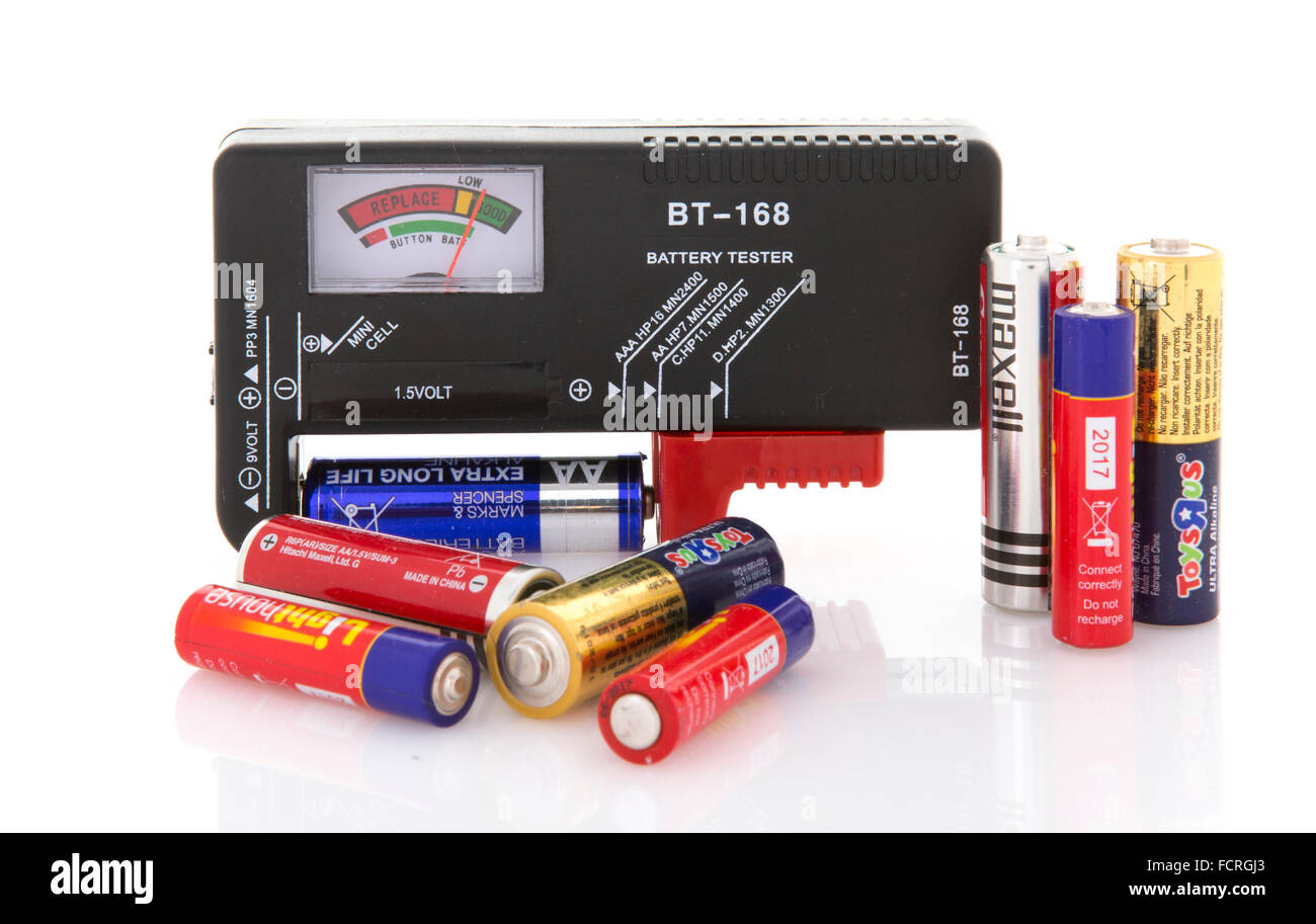 Battery Tester with assortment of dry cells for testing on a white background - Stock Image