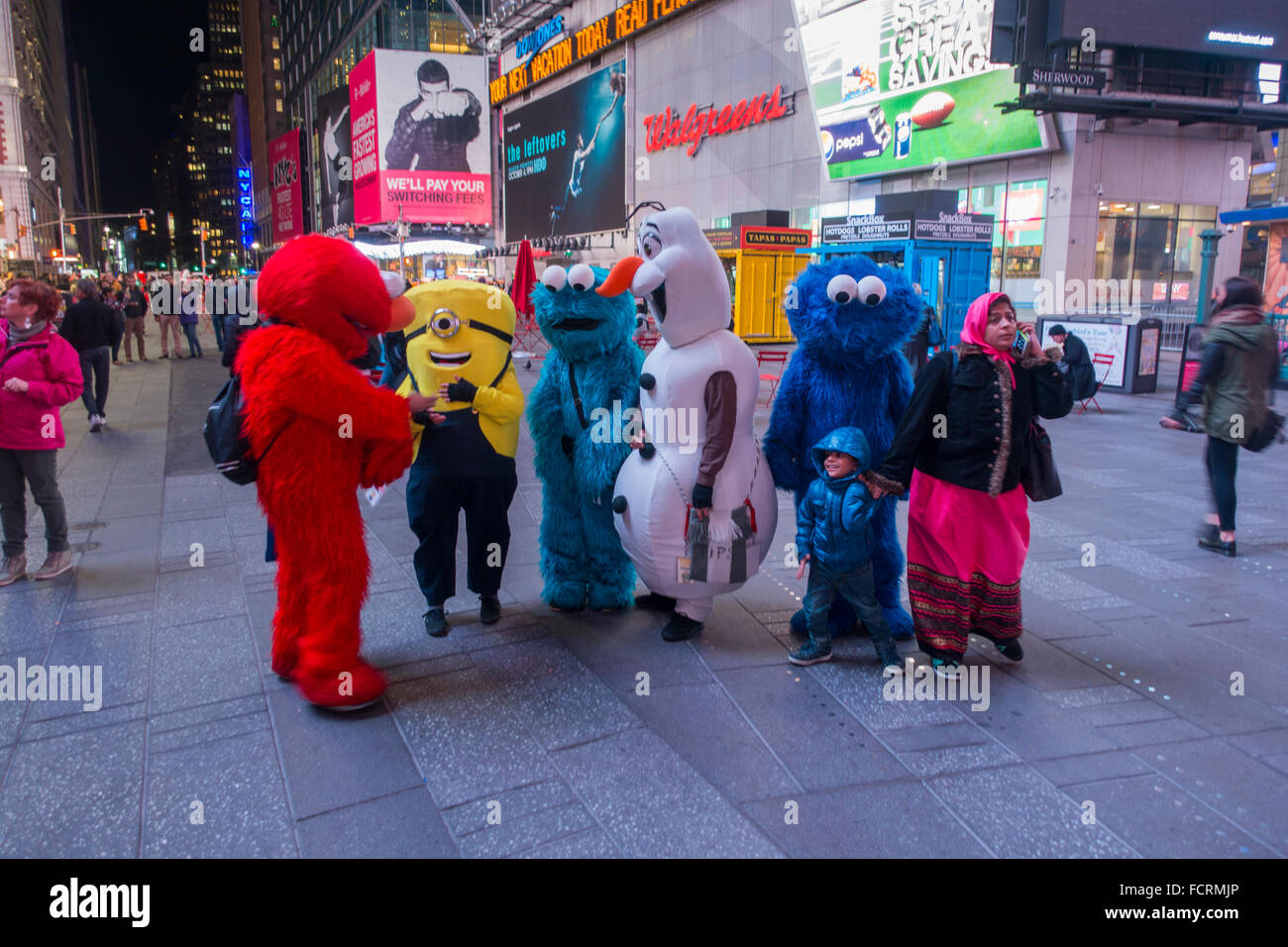 tourists posing cartoon characters times square stock photo