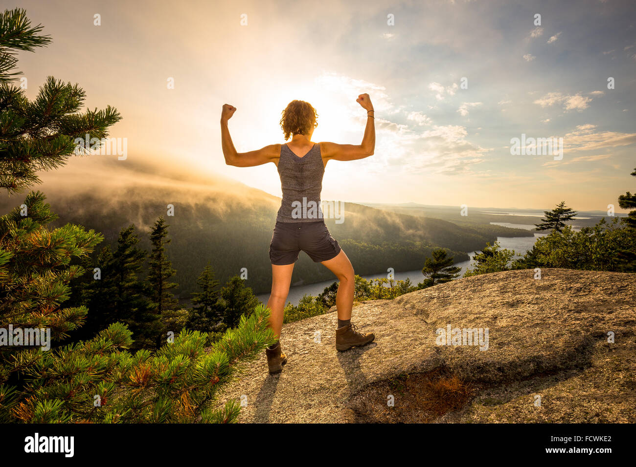 A young woman flexes on a mountaintop overlook in Acadia National Park, Mount Desert Island, Maine, New England, - Stock Image