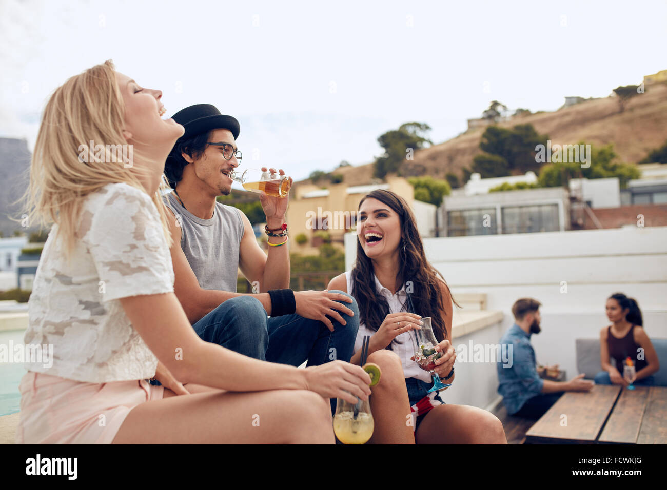 Happy young people having drinks and enjoying while their friends sitting and talking to each other in the background. - Stock Image