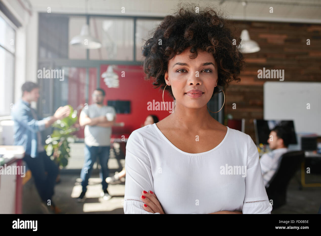 Portrait of woman standing in busy creative office looking at camera. Attractive female creative professional in - Stock Image