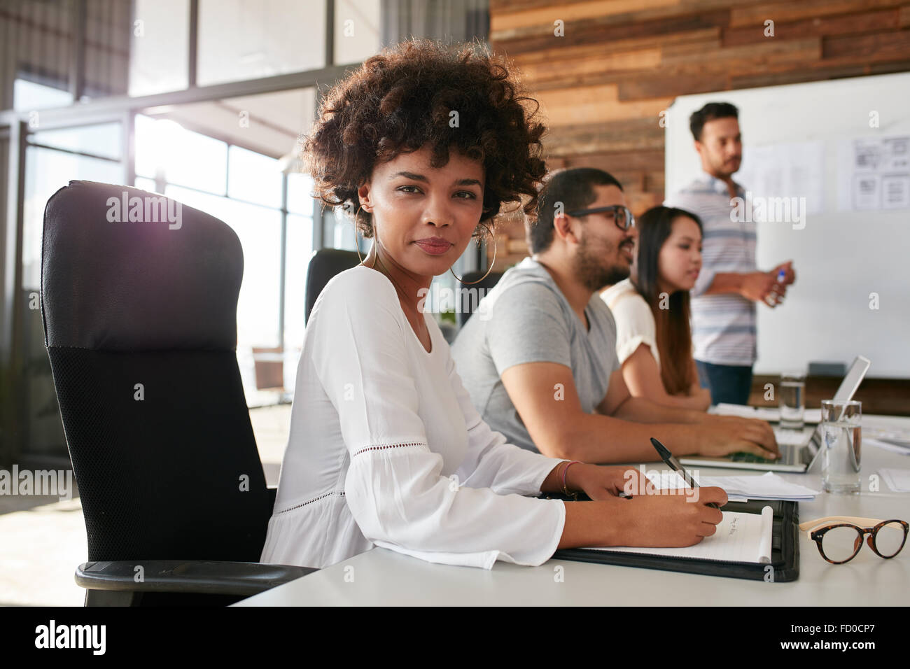 Portrait of confident businesswoman sitting at a business presentation with colleagues in boardroom. African woman - Stock Image