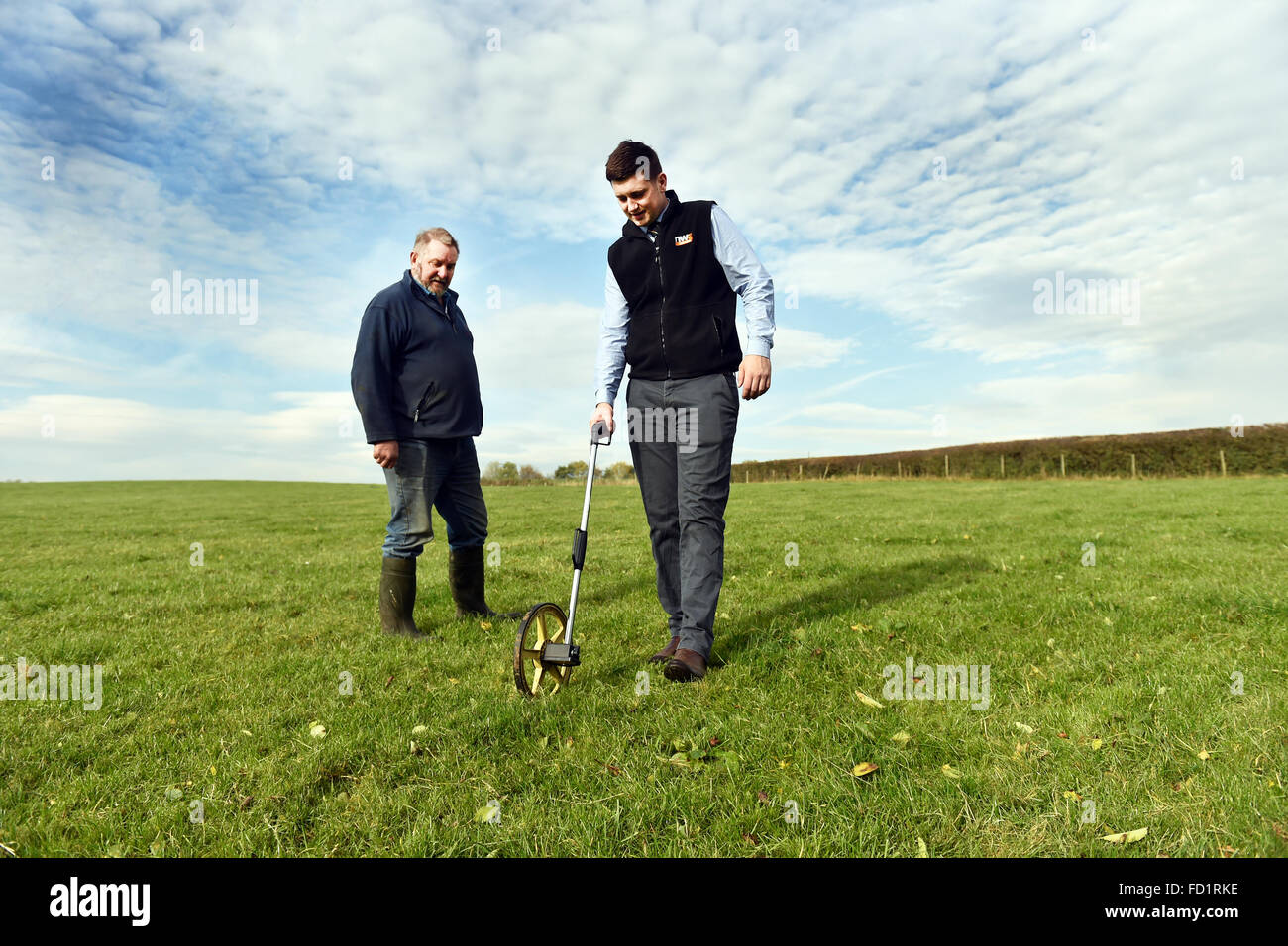 An auctioneer surveys some  land with a  farmer, Milnthorpe, Cumbria UK - Stock Image