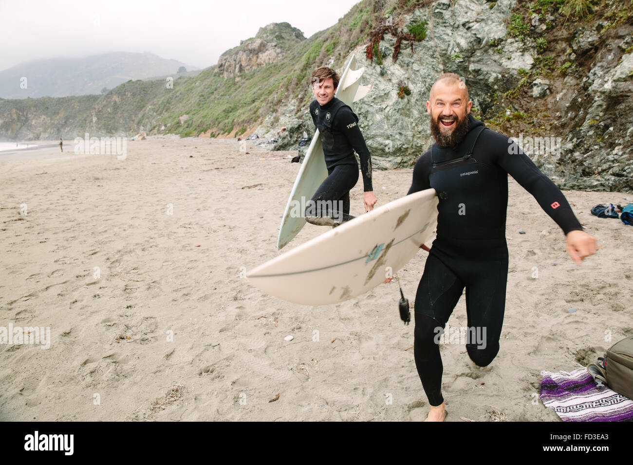Two surfers goof around on the beach before jumping in the water to catch waves in Big Sur, California. - Stock Image