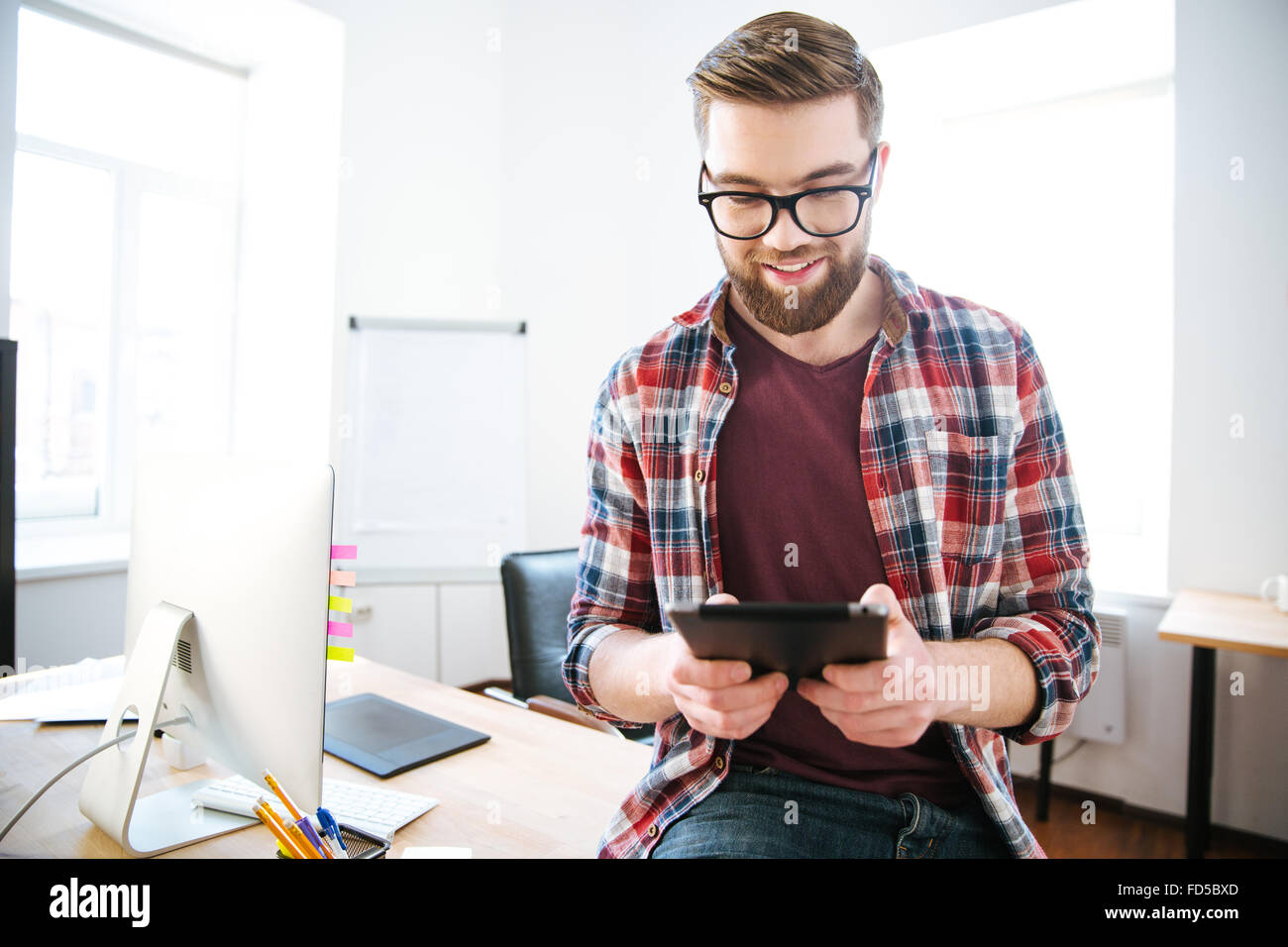 Happy handsome man with beard in plaid shirt and glasses sitting on the table in office and using tablet - Stock Image