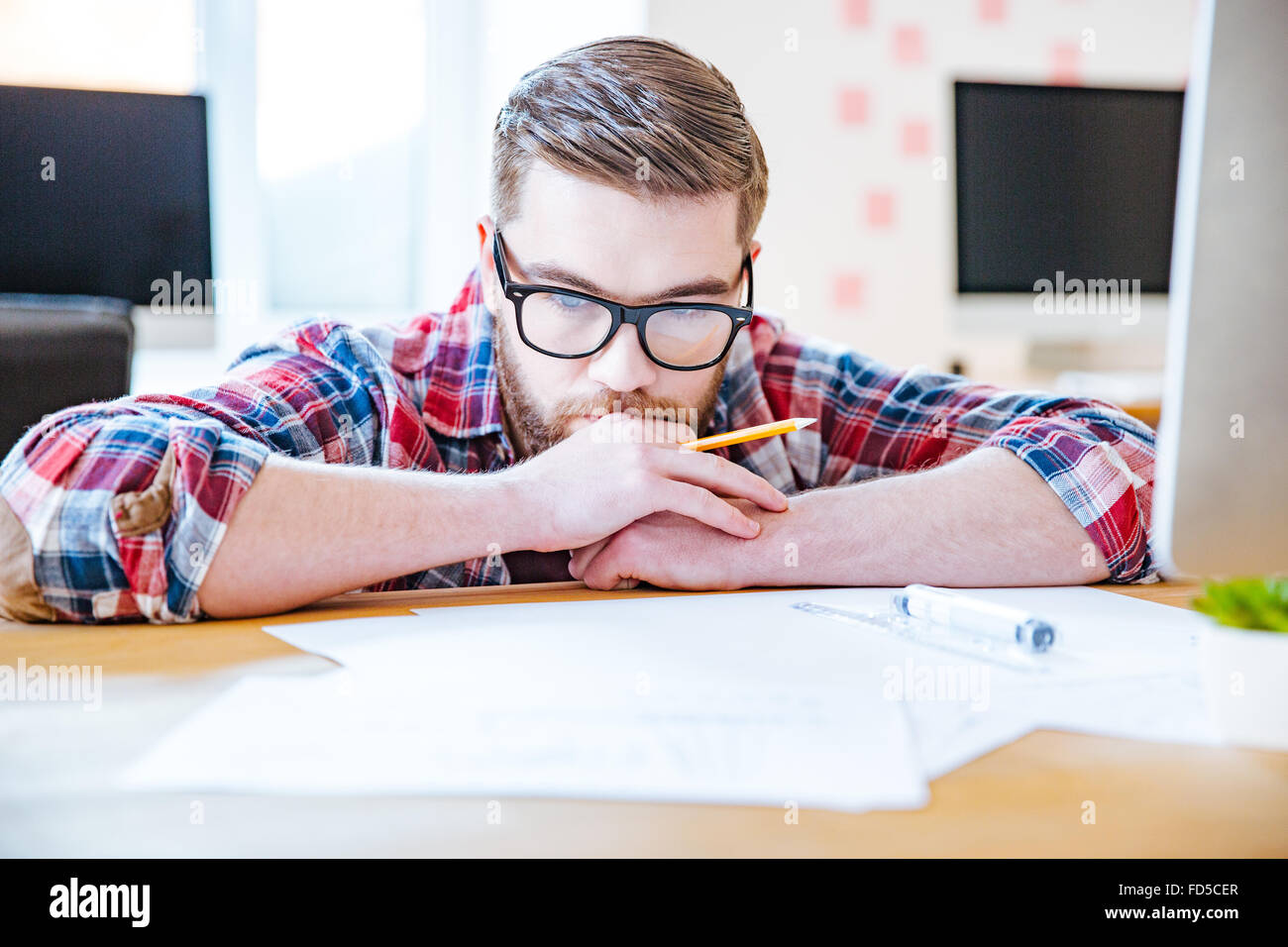 Thoughtful bearded young man in glasses working with blueprits using pencil and ruler in the office - Stock Image