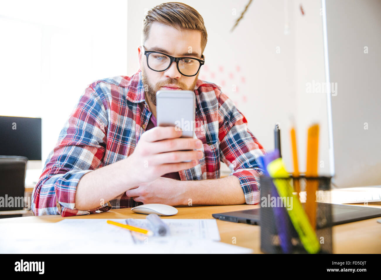 Handsome concentrated young man with beard in checkered shirt sitting at the table and using cell phone - Stock Image