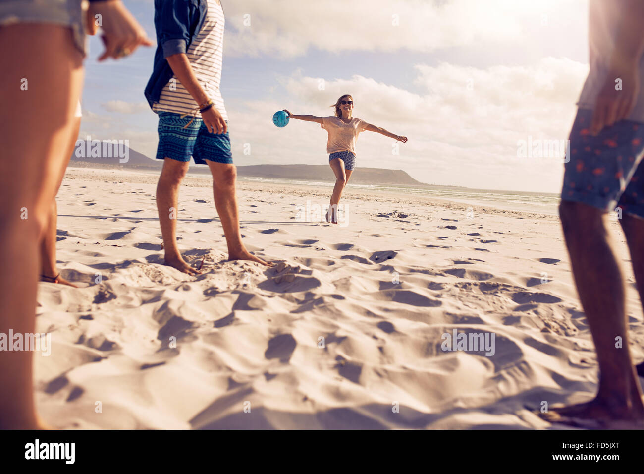 Low angle shot of young woman running on the beach with a ball with her friends standing in front. Group of friends - Stock Image