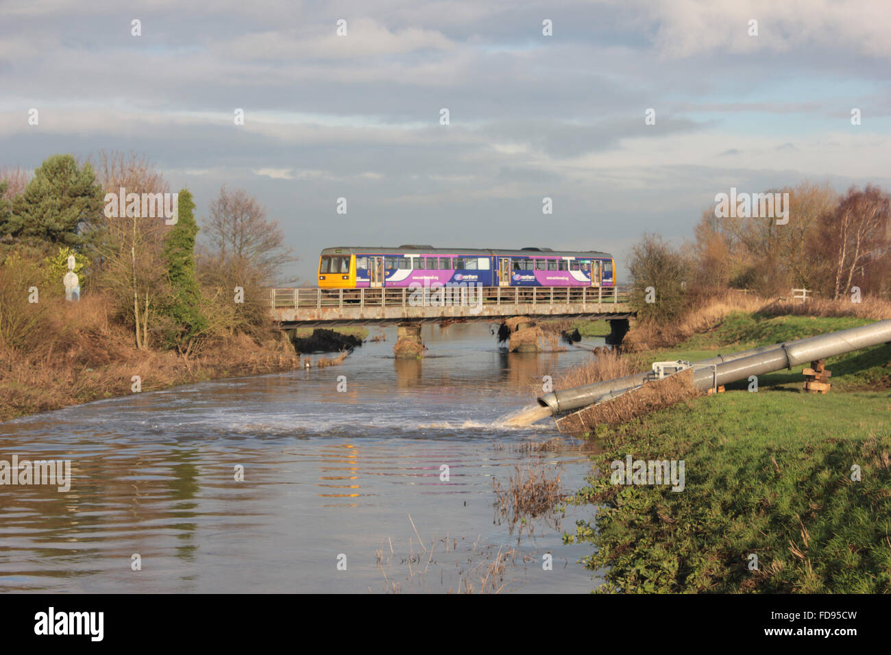 """A Northern train service formed of a """"Pacer"""" train crosses the River Douglas in Rufford - Stock Image"""