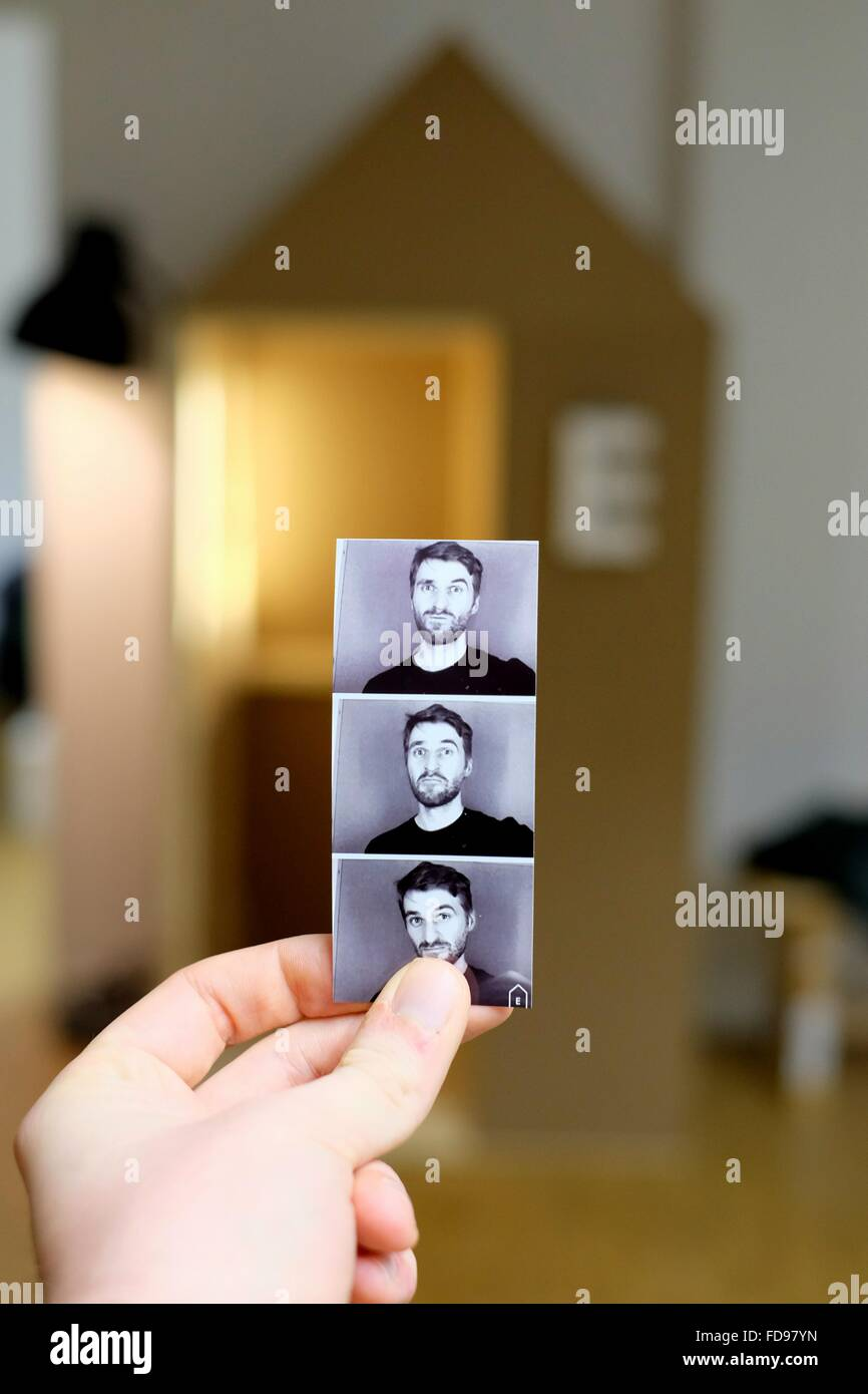 Man Holding Photo Booth Pictures - Stock Image