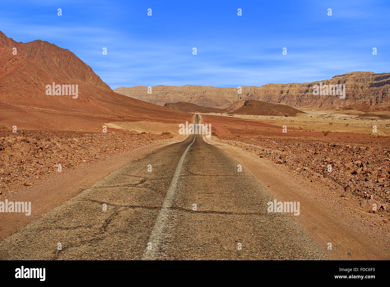 Paved road runs through Arava desert among red mountains in Timna national park, Israel. - Stock Image