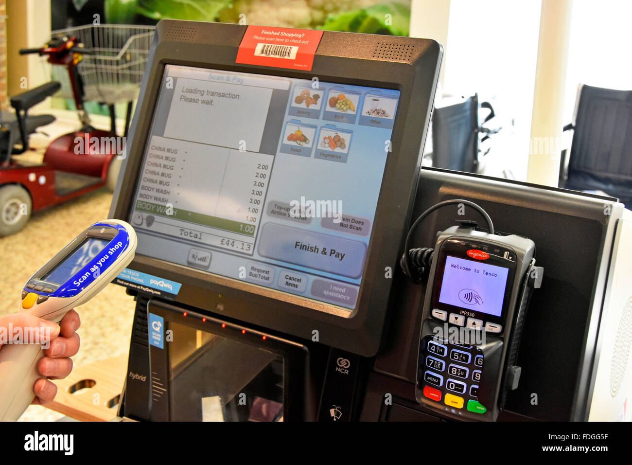 Tesco shopper aiming her Scan as you shop device to upload shopping items onto screen for payment & self checkout Stock Photo